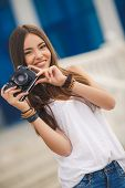 Beautiful young woman with a camera in the city.