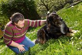 stock photo of disability  - disabled woman on a lawn is stroking a dog - JPG