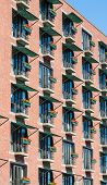 stock photo of geranium  - An old brick building in Boston with many balconies and geraniums in window boxes - JPG