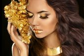 Golden Makeup Eyes Closeup. Beautiful Young Woman In Gold With Flowers Isolated On Black Background.