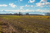 foto of torino  - Landscape of cultivated fields and farms with the snowcapped Alps in the background in late winter season - JPG