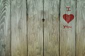 foto of graffiti  - Red graffiti message of I love you with heart shape on right side of weathered old grungy plank fence - JPG