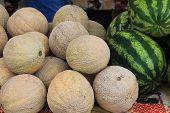 stock photo of cantaloupe  - Cantaloupe and watermelons for sale at a farmer