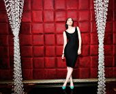 Woman in black dress standing against red velours wall