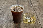 Delicious Ice Coffee Americano  With Cigarette On The Old Wooden Table