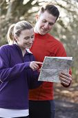 Couple Orienteering In Woodlands With Map And Compass
