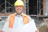 Builder in helmet with a drawing plan