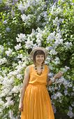 stock photo of orange blossom  - European lady in hat and orange dress with big lilac shrub in blossom - JPG