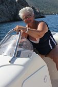 Mature woman enjoying her summer vacation on a boat