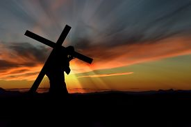 stock photo of calvary  - Christ carrying cross up Calvary on Good Friday over dark and stormy sky - JPG