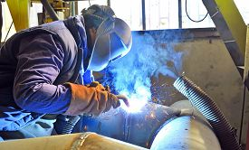 stock photo of welding  - Welder with protective mask welding metal and sparks