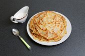pic of frizzle  - Frying homemade pancakes with sour cream on dark table - JPG