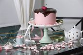 stock photo of cake stand  - Pink Cherry Cake Topped with Chocolate Ganache on Cake Stand Surrounded by Peppermint Candies on Glass Table with Polka Dot Tea Pot - JPG