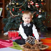 stock photo of miracle  - Little boy in Christmas decorations expect a miracle - JPG