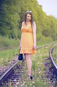 picture of train track  - Pretty woman in dress standing on the train tracks - JPG