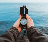 pic of pov  - Tourist woman searching direction with a compass on stone coastline near the sea close - JPG