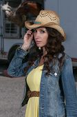 stock photo of country girl  - Beautiful young country girl woman wearing a stylish cowboy hat - JPG