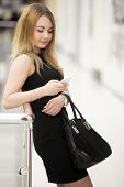 pic of dress-making  - Attractive relaxed young woman holding suede handbag wearing black dress making call using app on cellphone messaging in shopping center - JPG