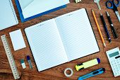picture of neat  - High Angle View of Office or School Supplies Neatly Organized Around Open Note Book with Blank Page on Wooden Desk Top - JPG