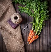 image of sackcloth  - Raw carrot with green leaves near scissors and rope on sackcloth and wooden background - JPG