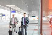 stock photo of carry-on luggage  - Middle aged businessmen with luggage rushing on railroad platform - JPG