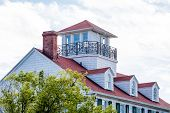 pic of gabled dormer window  - Cliassic white home with red roof dormers and widows walk - JPG