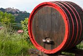 stock photo of wine-press  - Wine barrels and the hilltop town of Montepulciano Tuscany Italy - JPG
