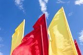 stock photo of flutter  - Red and yellow flags fluttering in the wind against blue sky - JPG