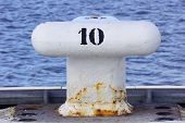 image of bollard  - A white metal bollard with sunlight and selective focus - JPG