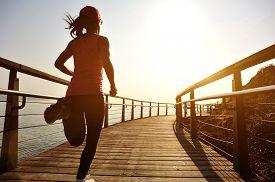 picture of japanese woman  - healthy lifestyle sports woman running on wooden boardwalk sunrise seaside - JPG