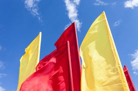 pic of flutter  - Red and yellow flags fluttering in the wind against blue sky - JPG