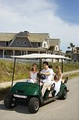 Caucasian family of four driving golf cart down residential street.