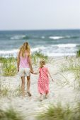 Caucasian pre-teen girl holding hands with younger Caucasian girl walking toward beach.