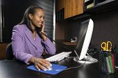 African-American young adult smiling business woman talking on phone and working at computer in offi