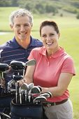 Caucasian mid-adult man and woman with golf clubs smiling and looking at viewer.