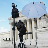 TV production set with camera and lighting equipment on tripods in front of Supreme Court building w