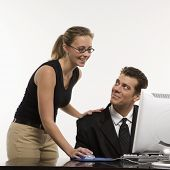 Caucasian mid-adult woman touching mid-adult man's shoulder and using mouse at computer.
