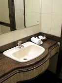 image of shower-cubicle  - a modern hotel bathroom counter with toiletry at the corner and shower cubicle reflected in the mirror - JPG
