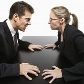 Caucasian mid-adult businessman and woman staring at each other with hostile expression.