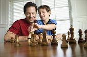 Caucasian mid-adult dad teaching chess to pre-teen boy.