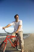 Caucasian mid-adult man posing on bicycle on beach.