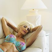 Tan Caucasion blonde middle-aged woman seductively lying in underwear on couch with arms raised smil