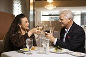 Caucasian mature adult male and prime adult female sitting at restaurant table toasting wine glasses