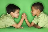 Hispanic and African American male child arm wrestling.