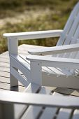 Close-up of Adirondack chairs on deck.