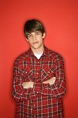 Portrait of Caucasian teen boy with arms crossed standing against red background wearing flannel shi