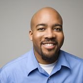 Portrait of African American man smiling against gray background.