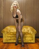 Attractive Caucasian woman in lingerie posing in retro room.