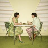 Caucasian mid-adult man and woman wearing vintage clothing sitting at 50's retro dinette set facing