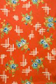 Close-up of red vintage fabric with colorful flowers printed on polyester.